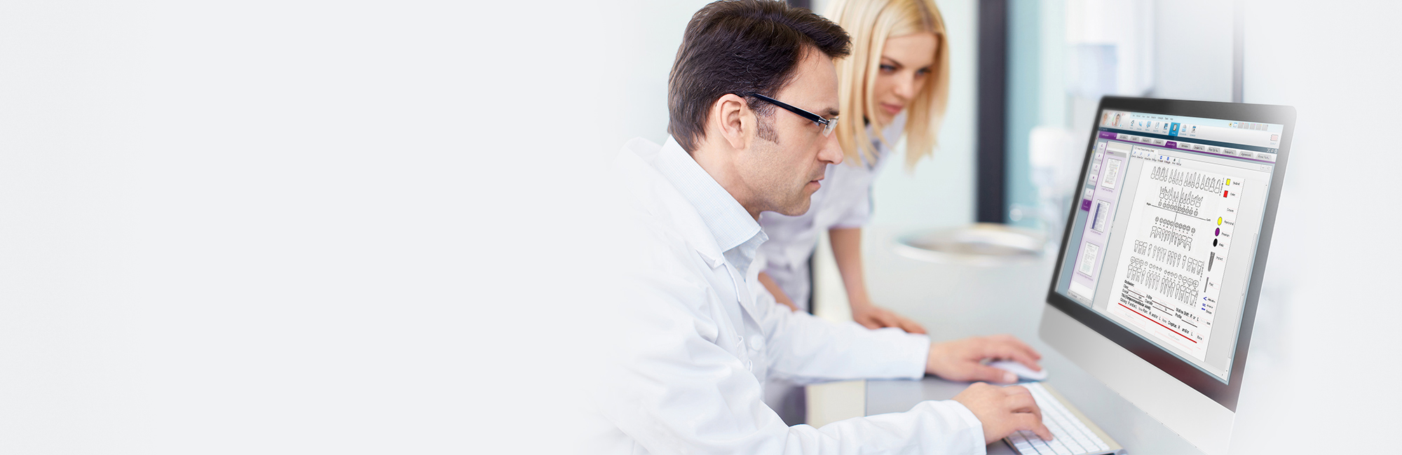 doctor using dental form software on computer with dental assistant